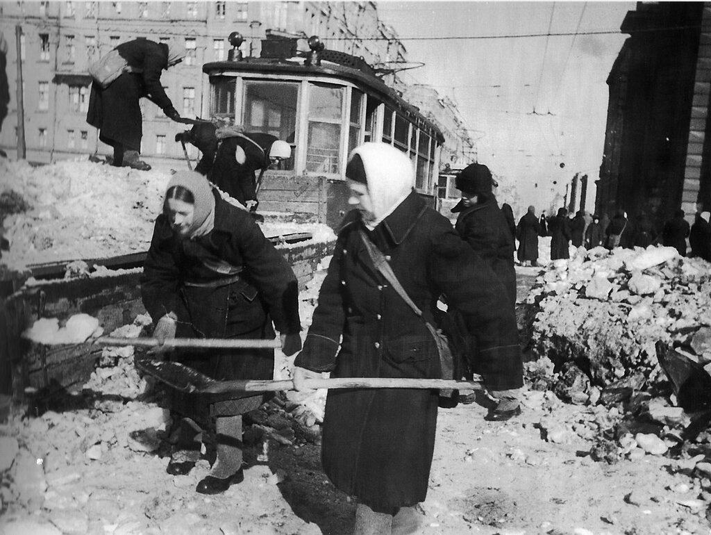 Бойцы местной противовоздушной обороны убирают снег на Международном проспекте блокадного Ленинграда. Март 1942 г